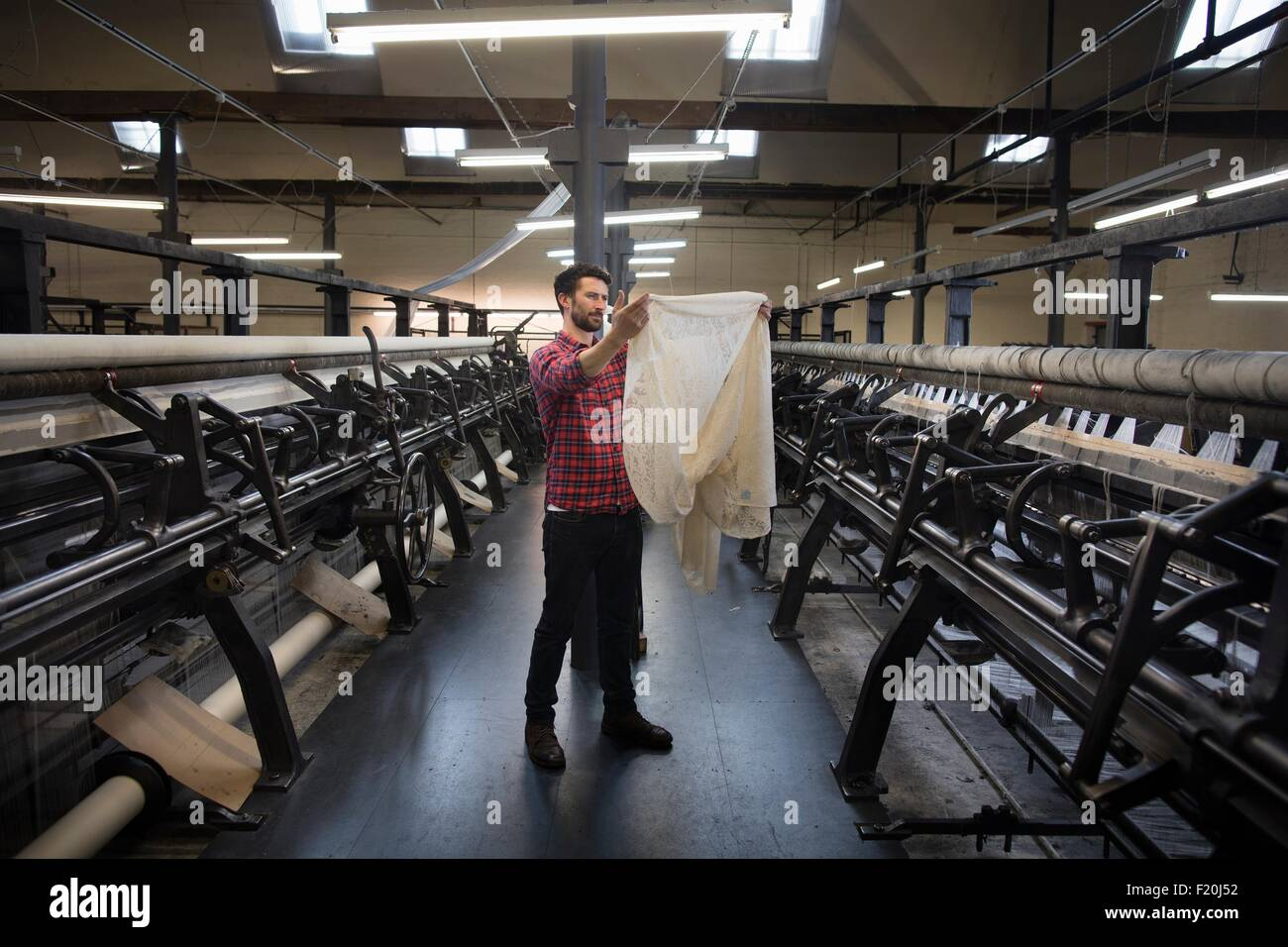 Portrait of male weaver examining cloth from old weaving machine in textile mill - Stock Image