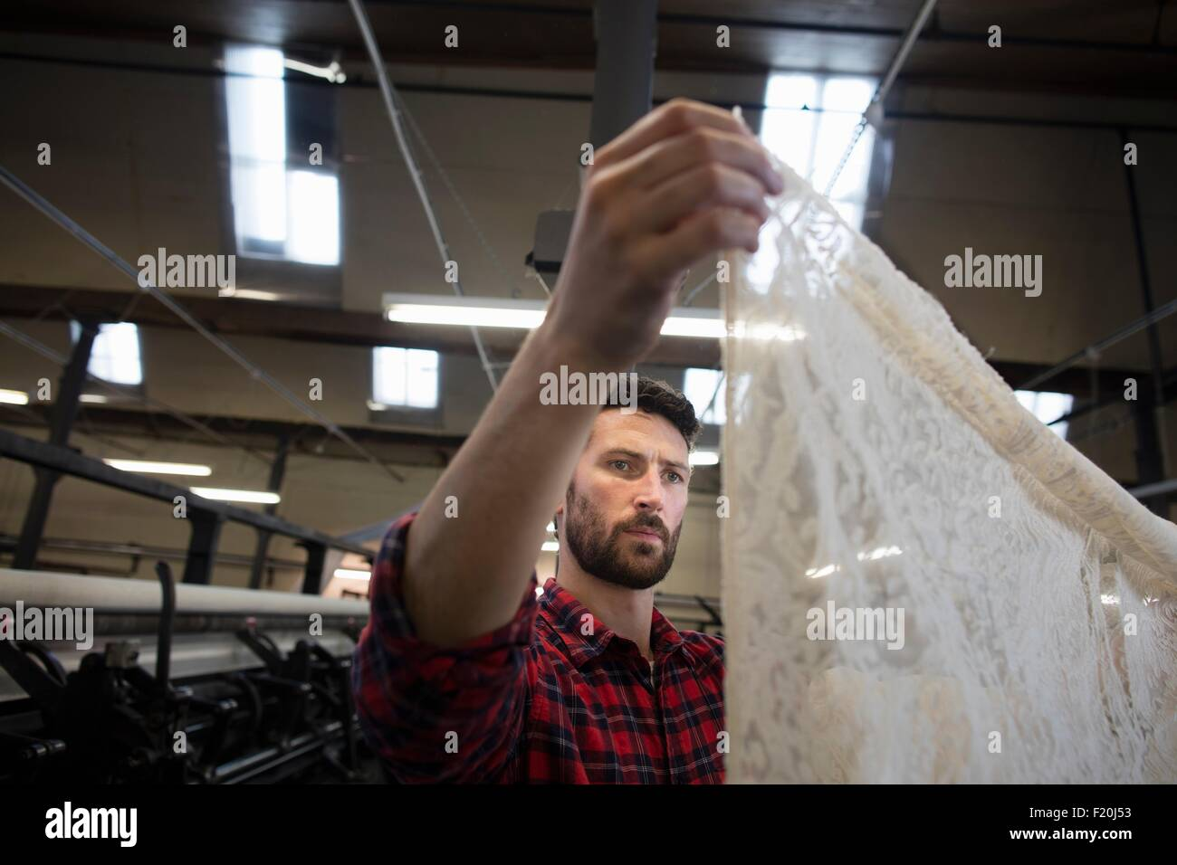 Portrait of male weaver examining lace cloth from old weaving machine in textile mill - Stock Image