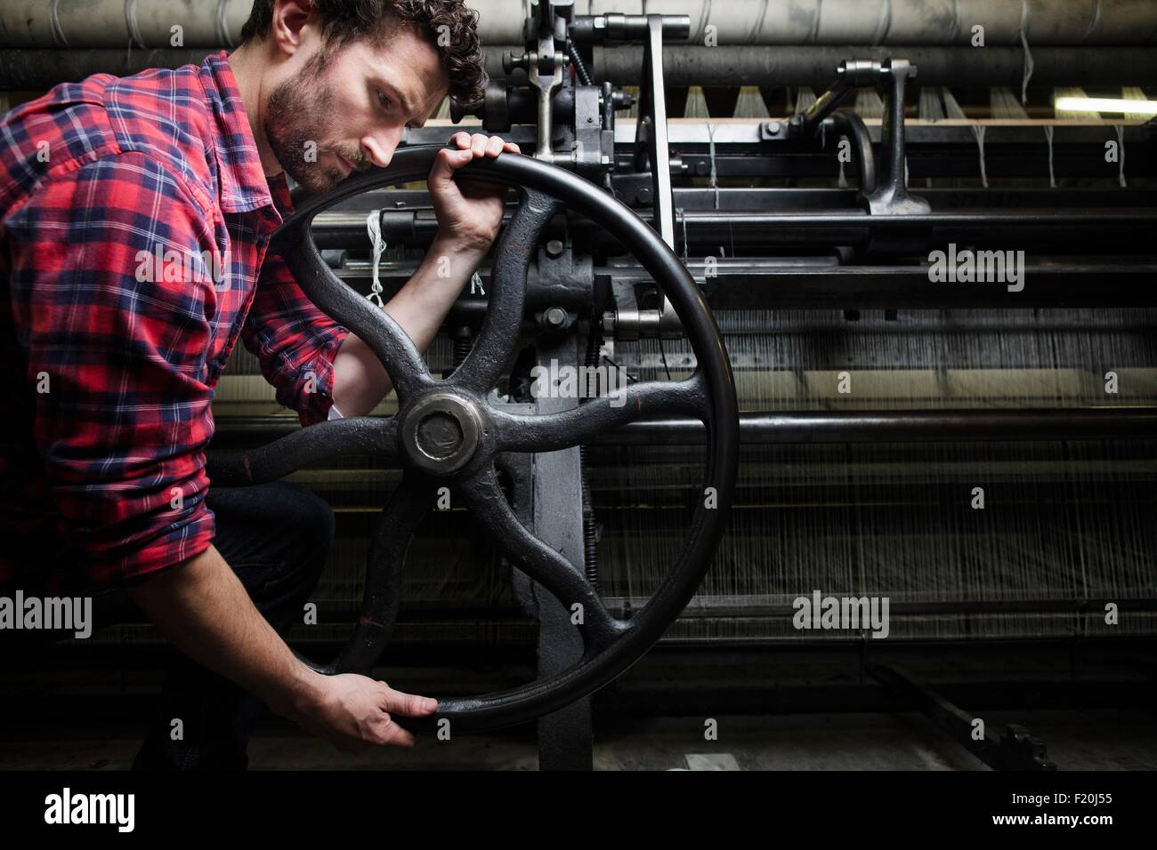 Male weaver turning wheel on old weaving machine in textile mill - Stock Image