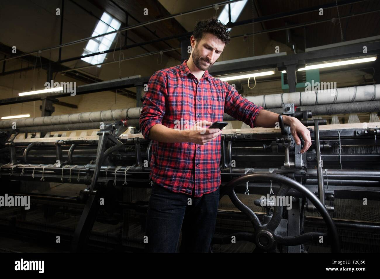Male weaver smartphone texting next to old weaving machine in textile mill - Stock Image