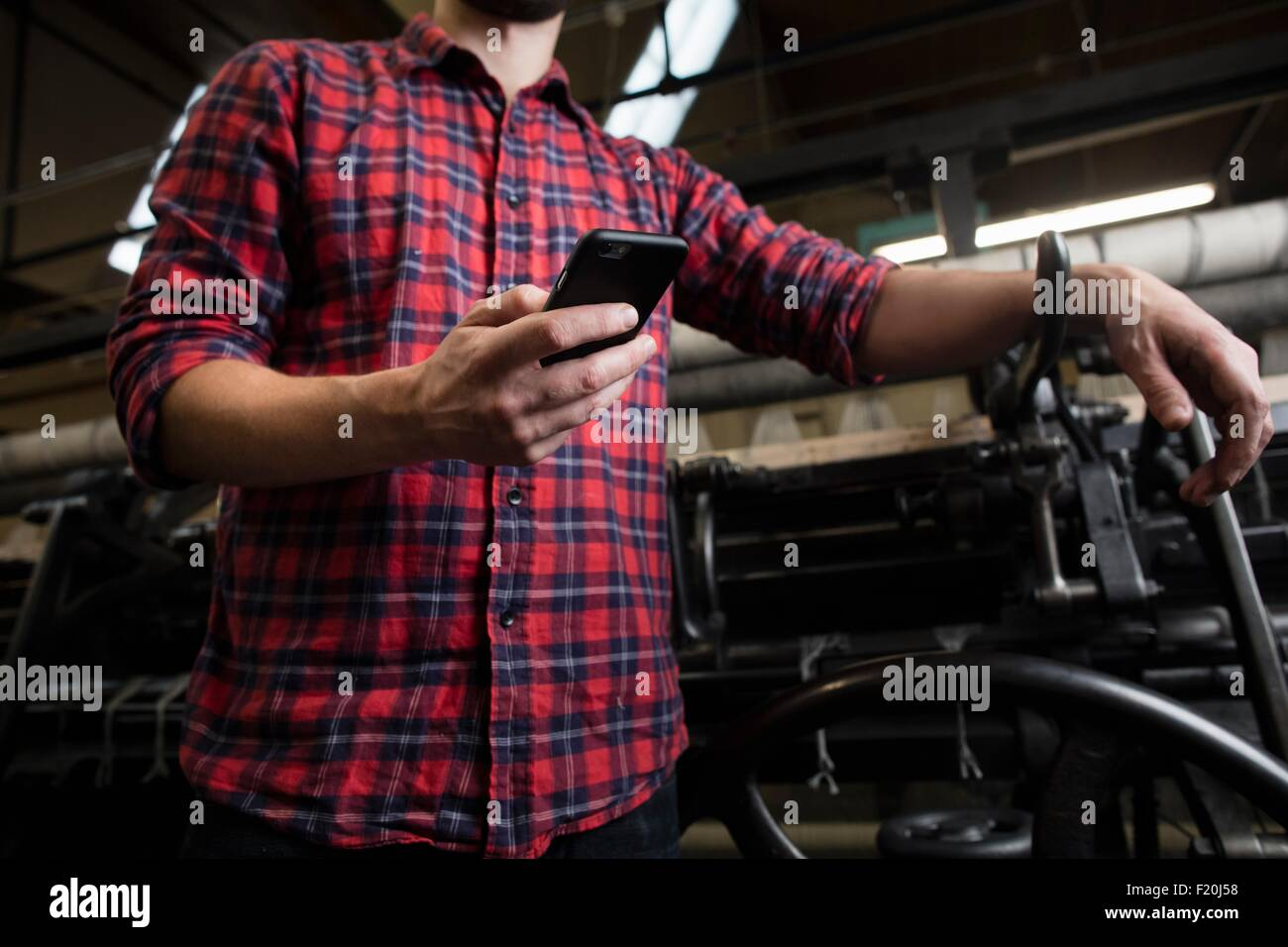Cropped shot of male weaver smartphone texting next to old weaving machine in textile mill - Stock Image