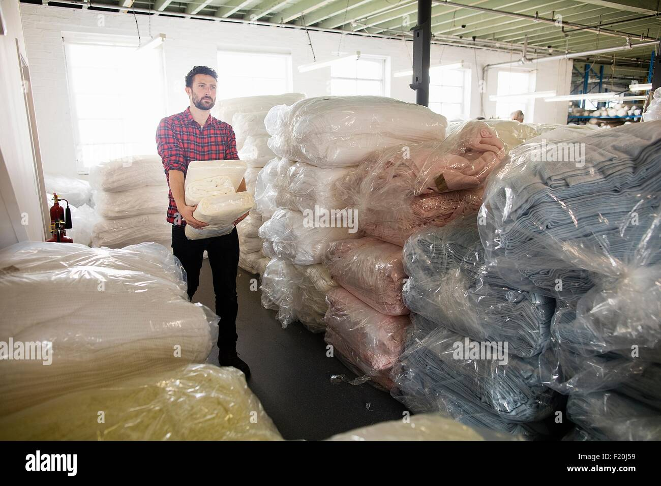Male weaver carrying orders in textile mill stockroom - Stock Image
