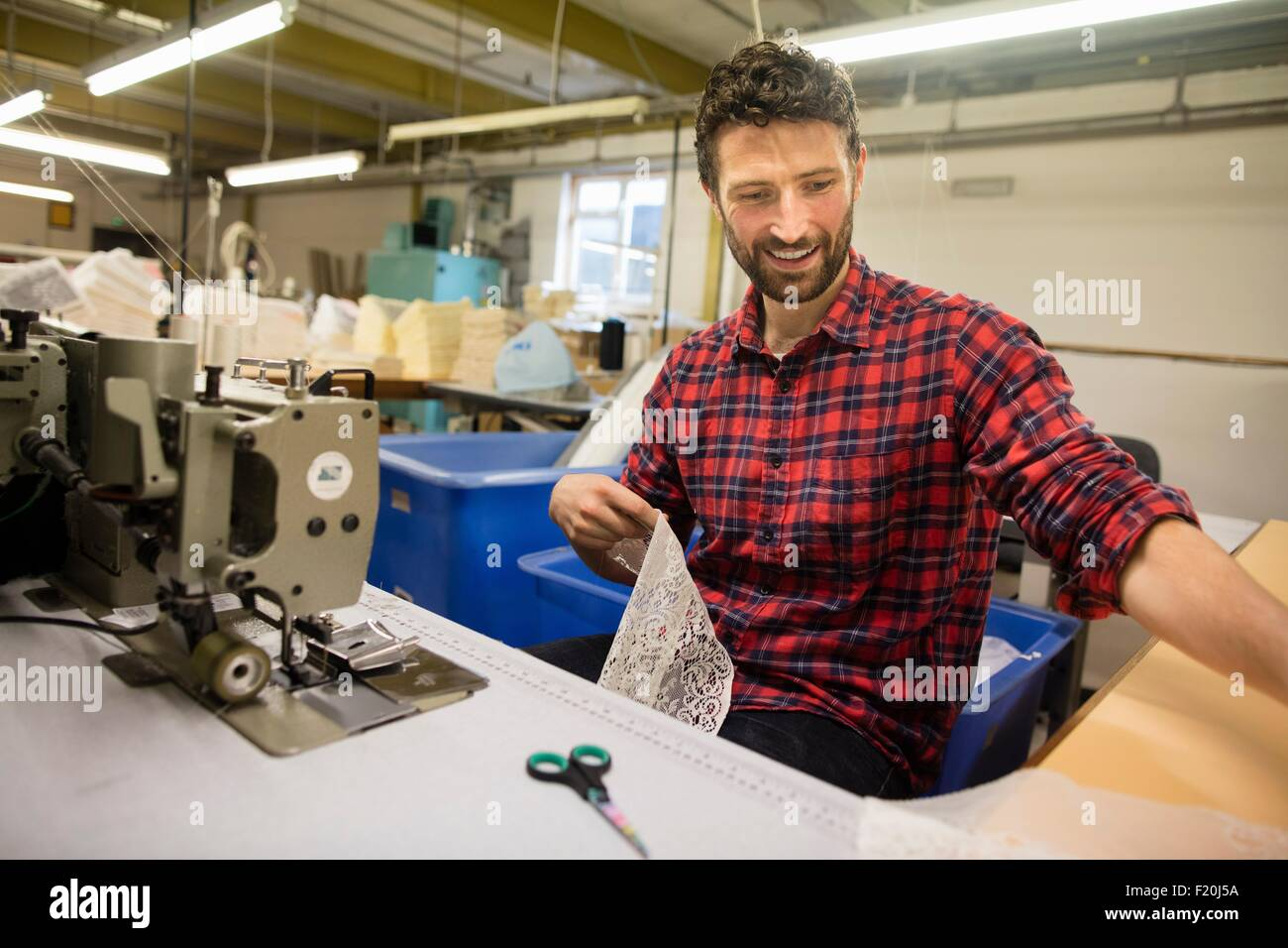 Male weaver finishing lace on sewing machine in old textile mill - Stock Image