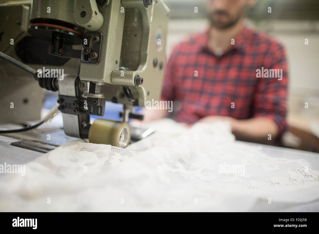 Male weaver sewing lace on sewing machine in old textile mill - Stock Image