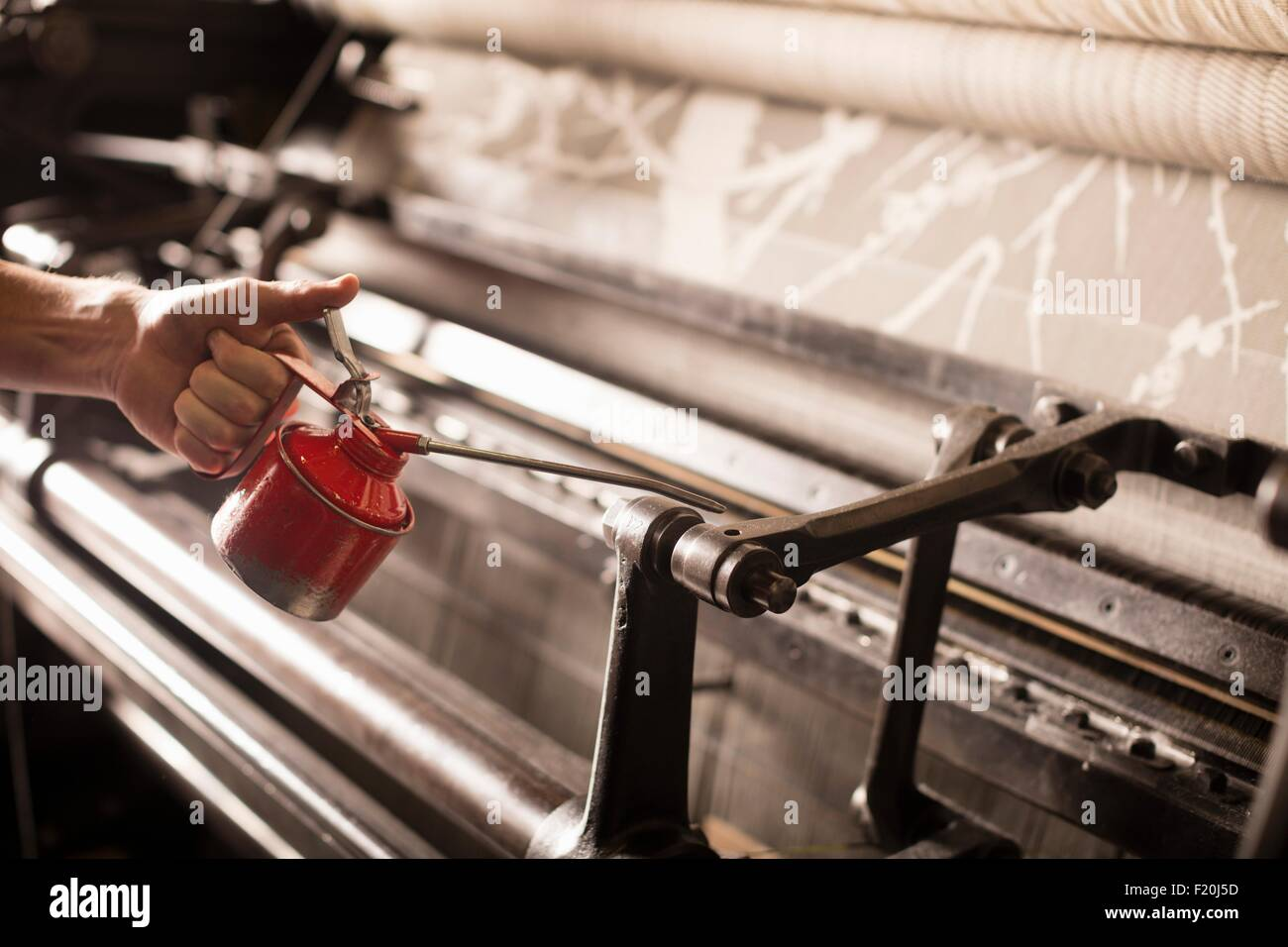Hand of male weaver oiling old weaving machine in textile mill Stock Photo