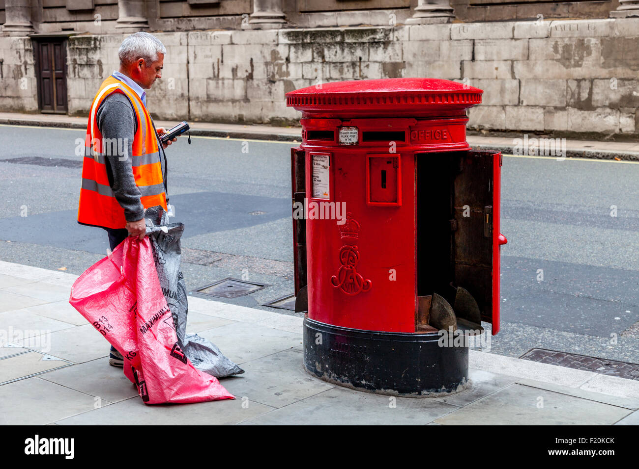 A Royal Mail Worker Collects The Mail From A Post Box In Central London, England - Stock Image