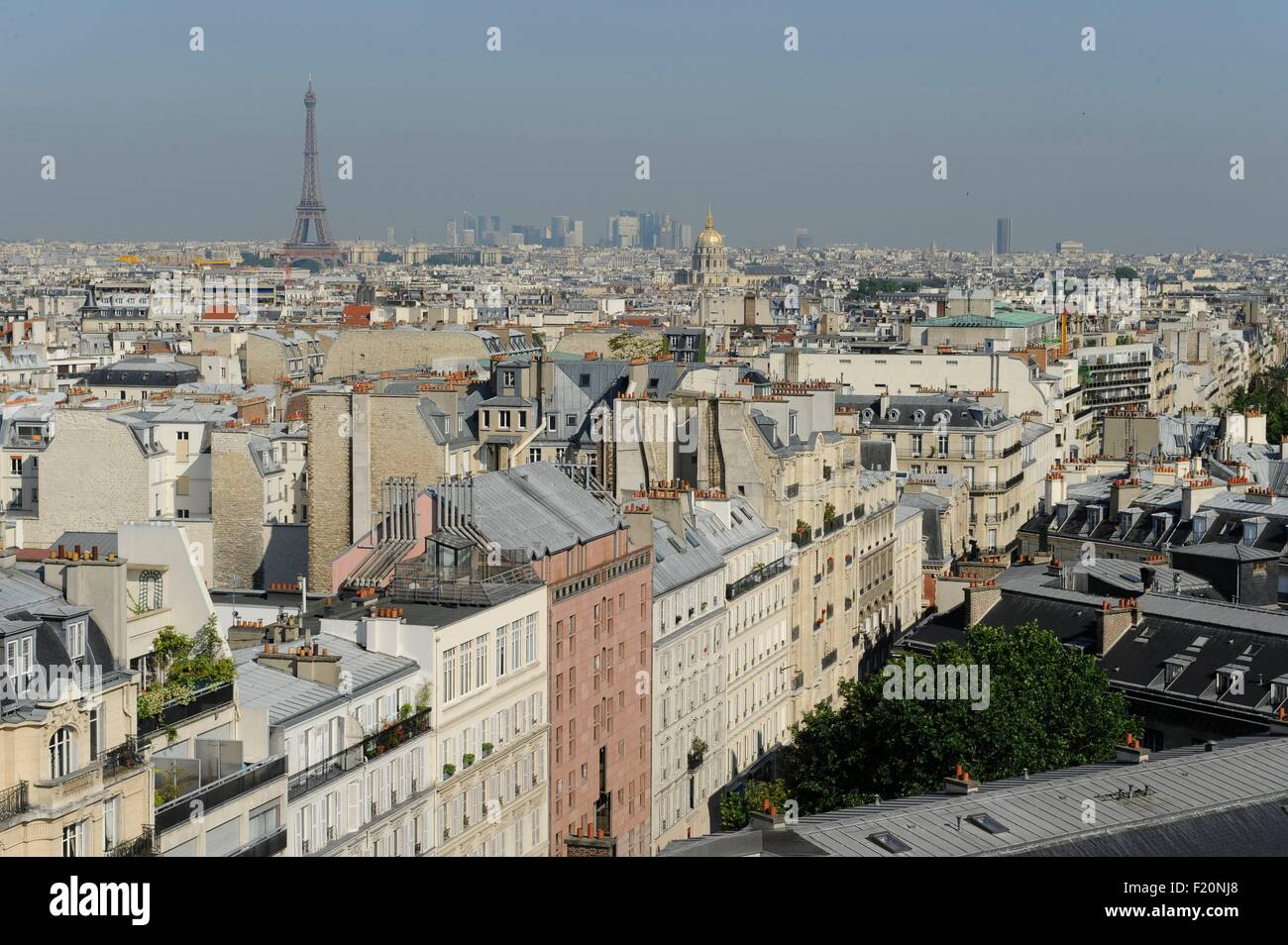 France, Paris, Emerging amid the rooftops of Paris, the Eiffel Tower, In the background, the gilded dome of Les - Stock Image