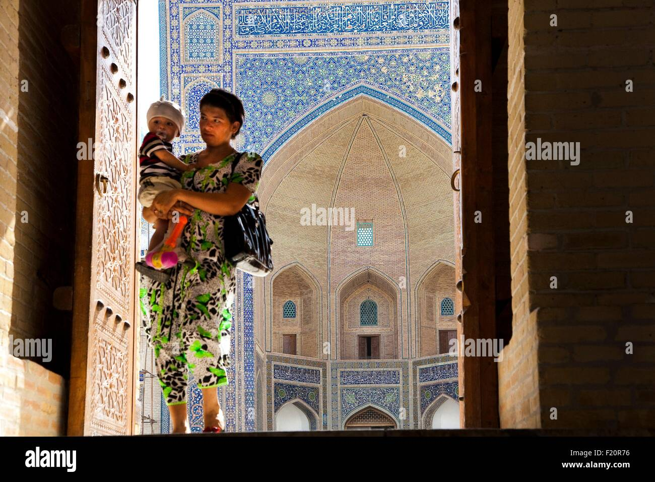 Uzbekistan, Bukhara, Miri Arab Madrassah, listed as World Heritage by UNESCO, a mother with her son crossing the - Stock Image