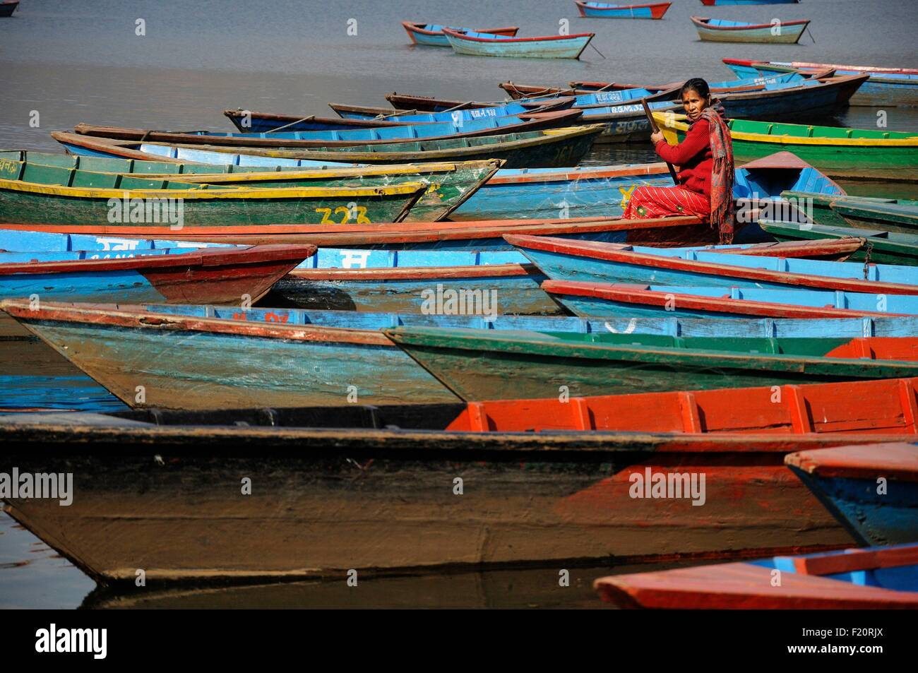 Nepal, Pokhara, woman in red among the colourful wooden boats on th lake Phewa Tal - Stock Image