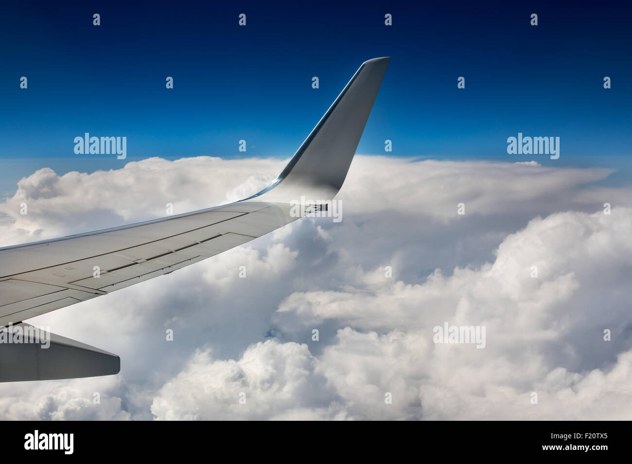 Part of airplane wing on sky and clouds background - Stock Image