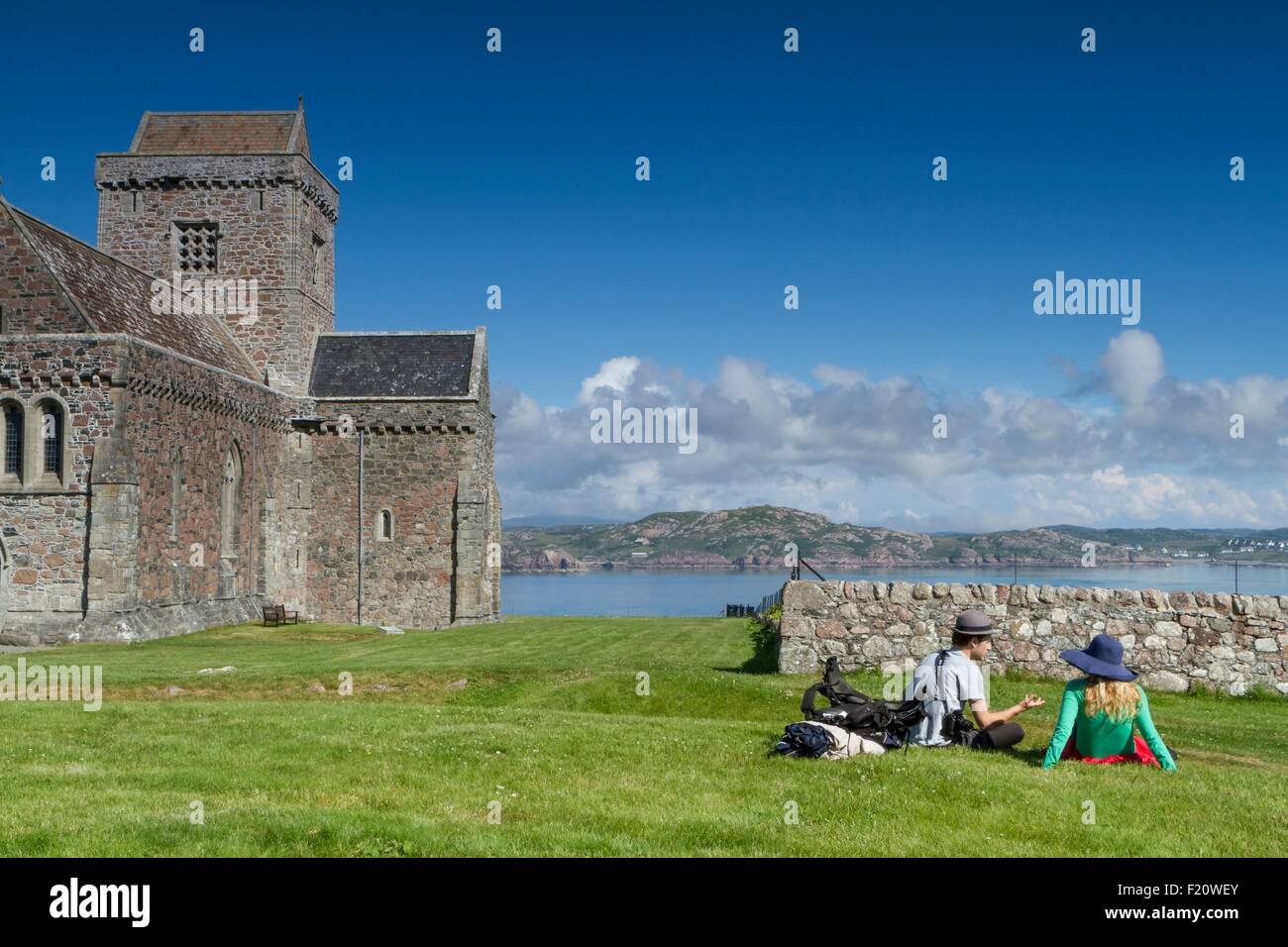 United Kingdom, Scotland, Hebrides, Isle of Iona, Iona Abbey, couple relaxing in the grass next to the Iona Abbey - Stock Image