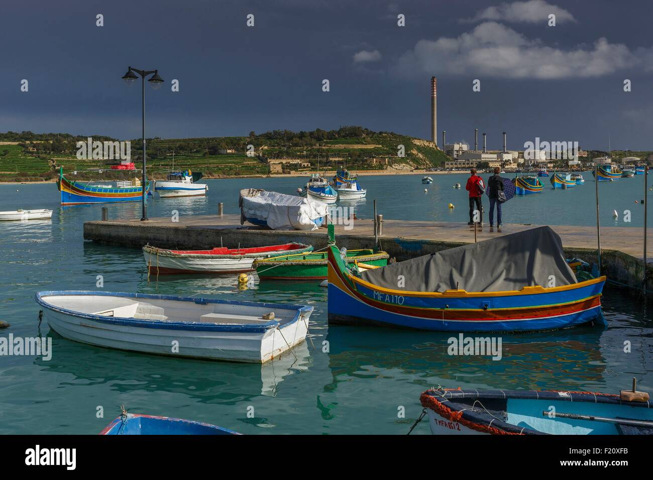 Malta, Marsaxlokk, onlookers walking on the docks of the fishing village under a cloudy sky - Stock Image