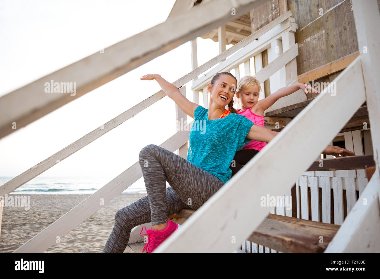 A young, happy mother shows her young daughter how to fly. They are playing and pretending to be seagulls, flying - Stock Image