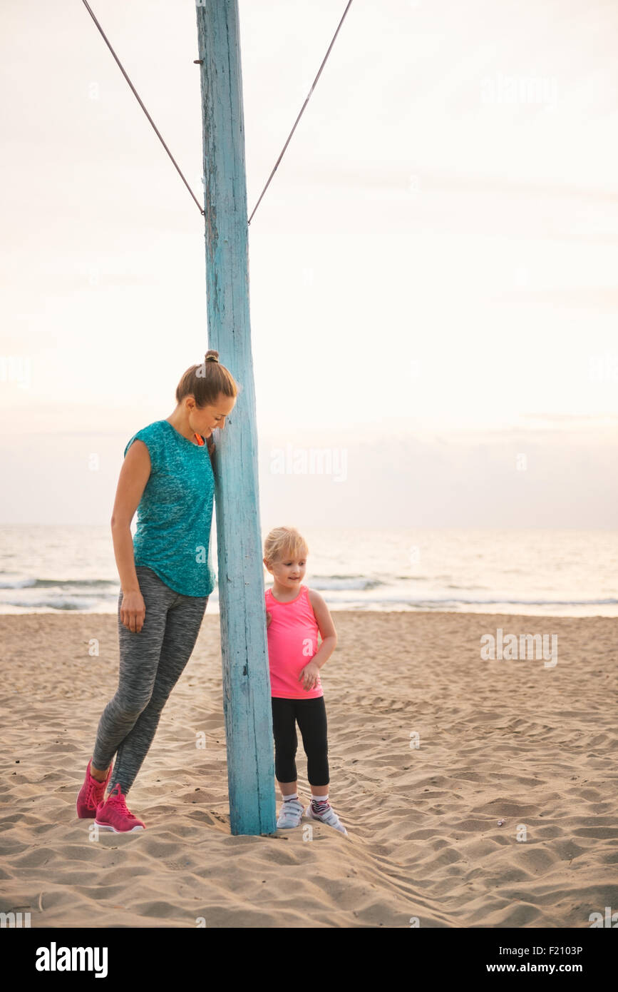 An anonymous young mother is leaning against a flagpole on the beach, looking down at her daughter, who is standing - Stock Image