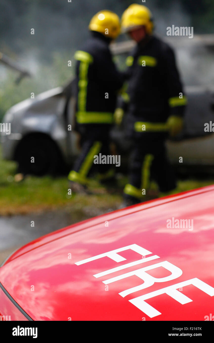 Essential Services, Firemen putting out fire in a car. - Stock Image