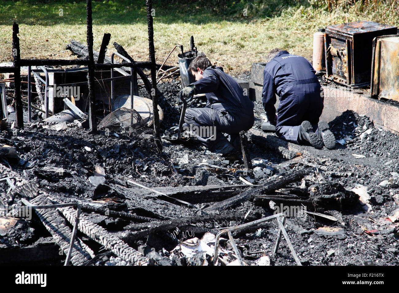 Essential Services, Fire, Forensic team examing charred ruin for potential causes of fire. - Stock Image