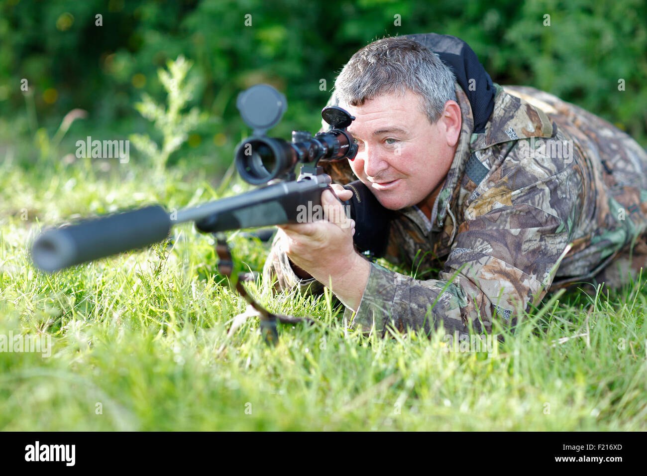 Sport, Gun, Shooting, Sniper wearing camoflage holding rifle with powerful scope and noise reduction muzzle. - Stock Image