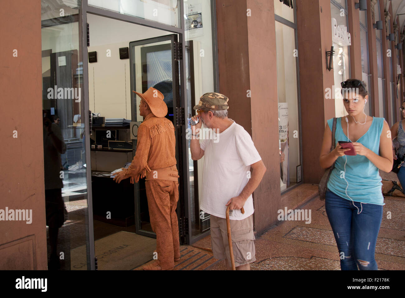 Living statue standing in doorway speaking to shop assistants while a passerby looks puzzled, a shop in Via Indipendenza - Stock Image