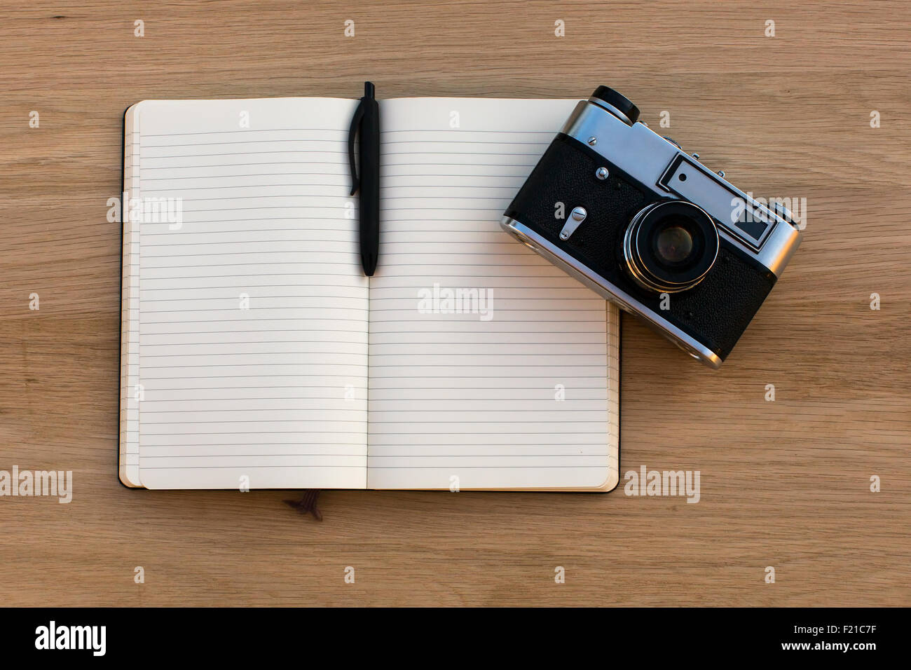Open notebook with a pen and a vintage film camera, top view on wooden texture of the table. Stock Photo