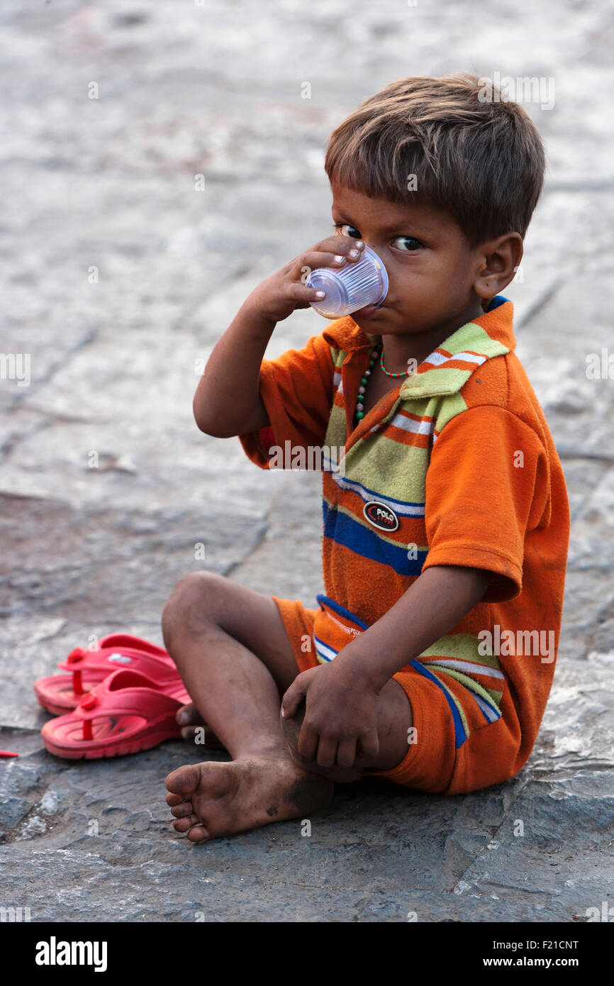 India, Maharashtra, Mumbai, Young boy drinking tea from a plastic cup while sitting on a pavement. - Stock Image