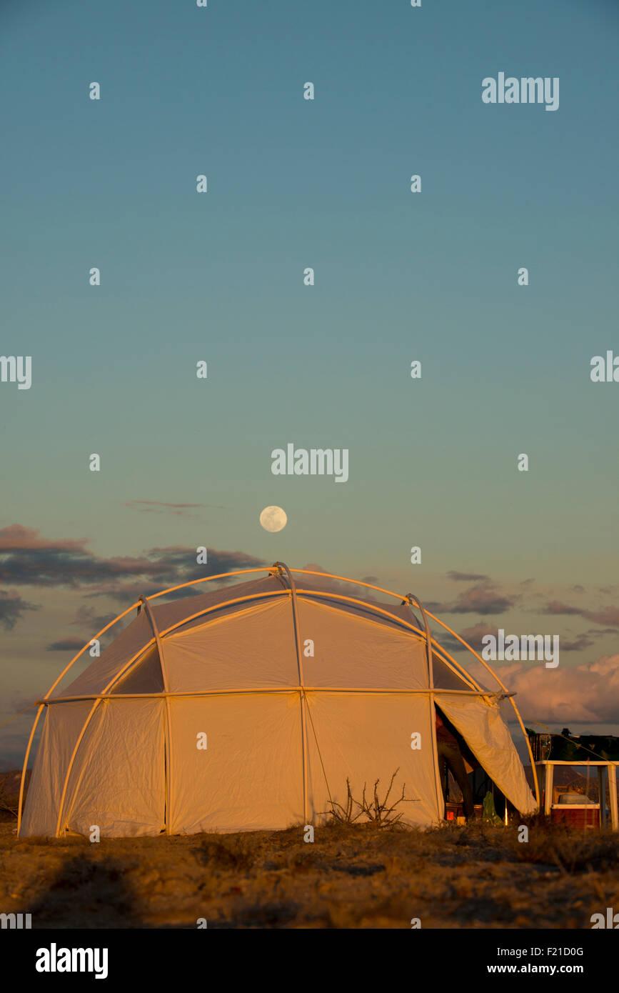 Mexico. San Ignacio Lagoon. Moon rising over tents. - Stock Image
