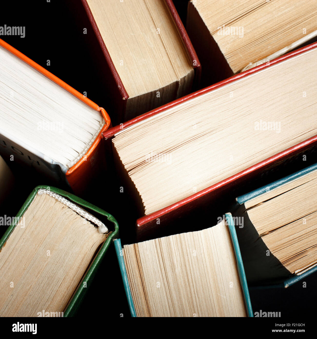 Old and used hardback books or text books seen from above. Books and reading are essential for self improvement, - Stock Image