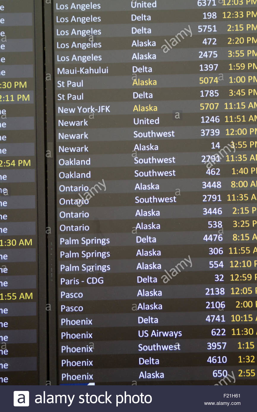An airport flight board at SeaTac Airport shows current flight status and delays - Stock Image