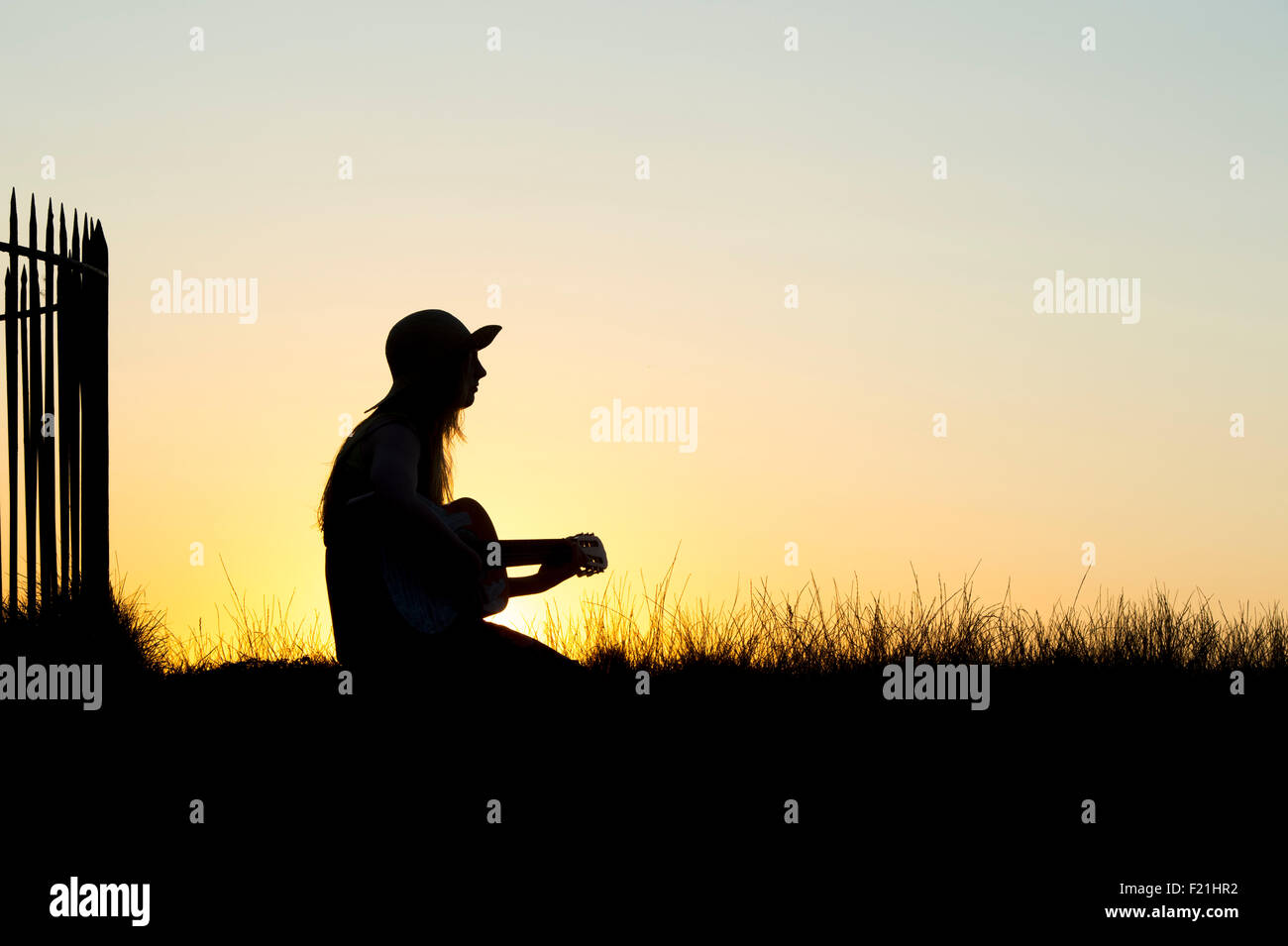 Teenage girl sat playing a guitar at sunset. Silhouette - Stock Image