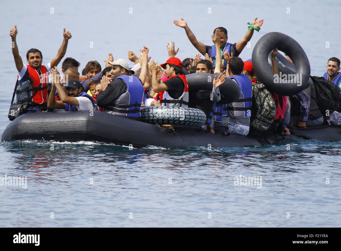 Lesbos, Greece. 9th September 2015. The refugees in an approaching small inflatable rubber dinghy cheer and wave - Stock Image