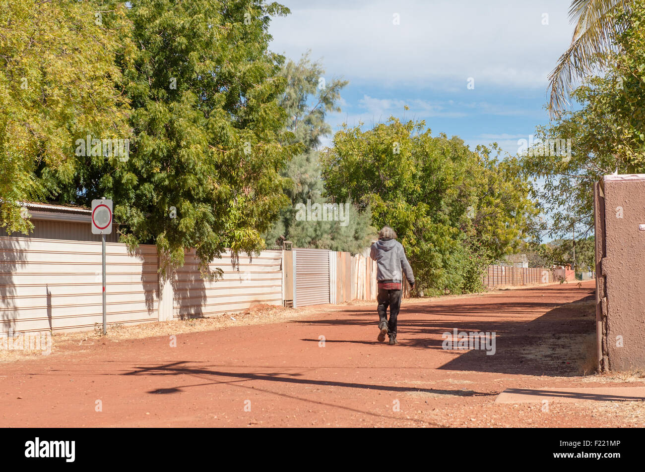 Aboriginal man walking down a residential street in the heart of Tennant Creek, Northern Territory, Australia - Stock Image
