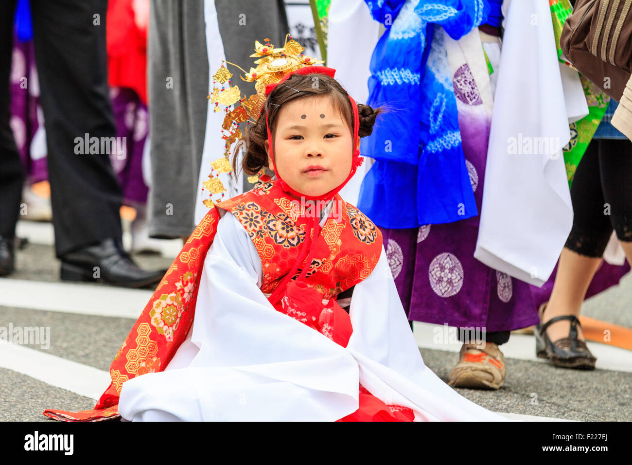 Japan, kawanishi, Osaka. Genji Festival. Little girl, Heian princess costume, sitting on street, bad tempered - Stock Image