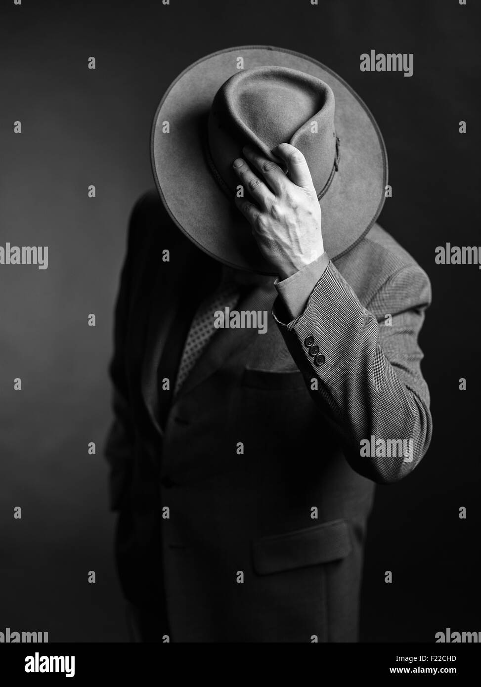 Male wearing dark suit and he covering face with a hat, black and white image - Stock Image