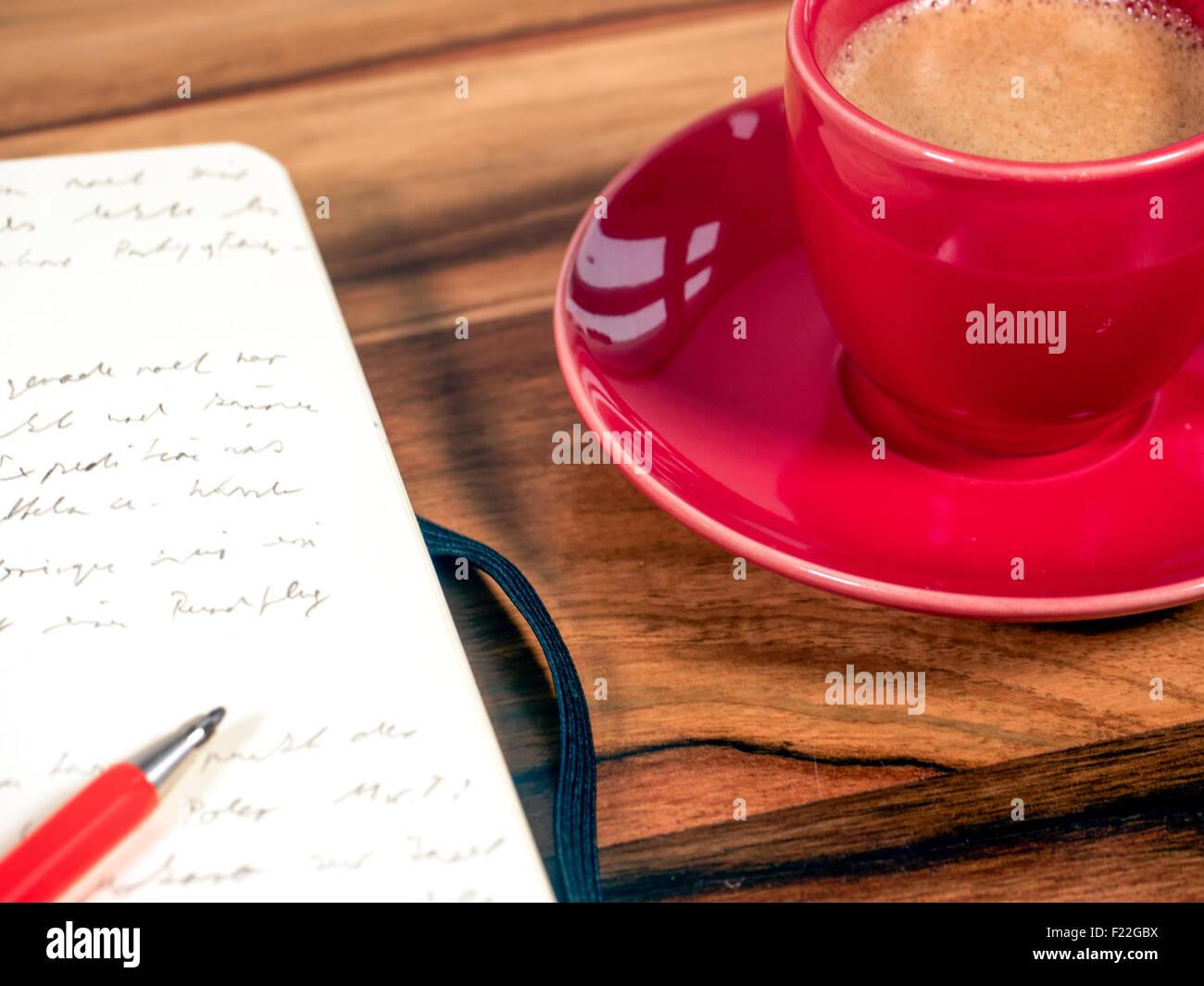 Notizbuch mit Kaffeetasse - Stock Image