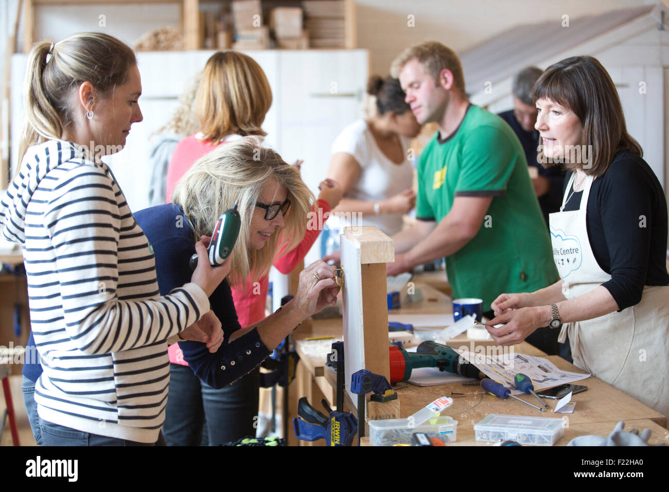 Middle aged people attending a Do-It-Yourself course learning basic carpentry skills, UK - Stock Image