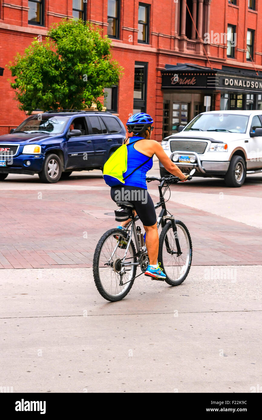 Woman exercising by riding her bicycle on the streets of Fargo ND in the summer months - Stock Image