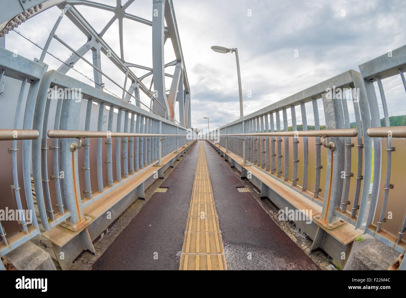 A fisheye shot of a ramp with hand rails on the sides leading to the center of the image. - Stock Image