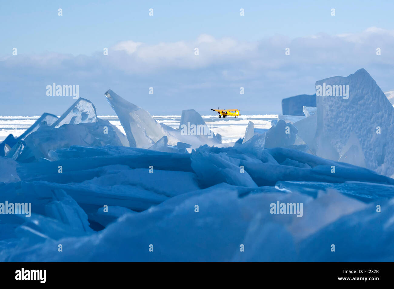 Low angle shot of plate ice jumbled on Lake Superior with yellow plane that landed on the frozen lake - Stock Image