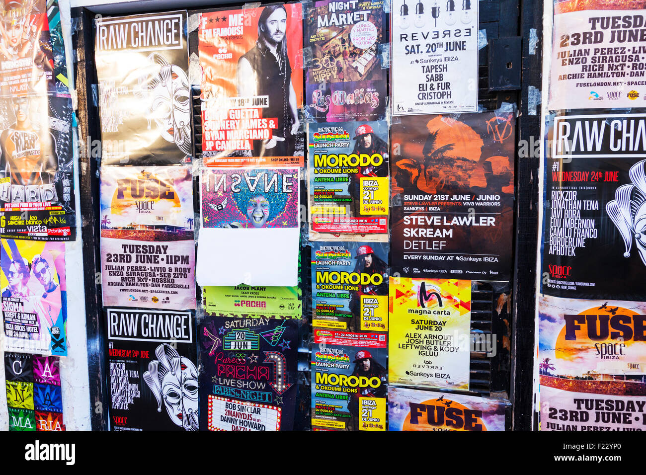 posters stuck on wall advertising bill posting adverts Ibiza clubs concerts events advertised - Stock Image