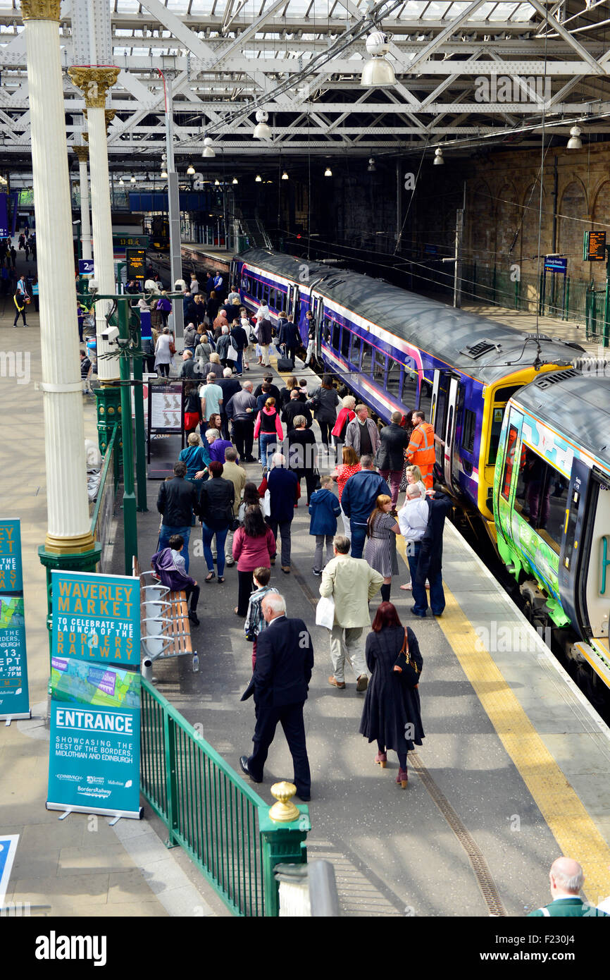 Train Edinburgh Waverley Station with passengers waiting to board. - Stock Image