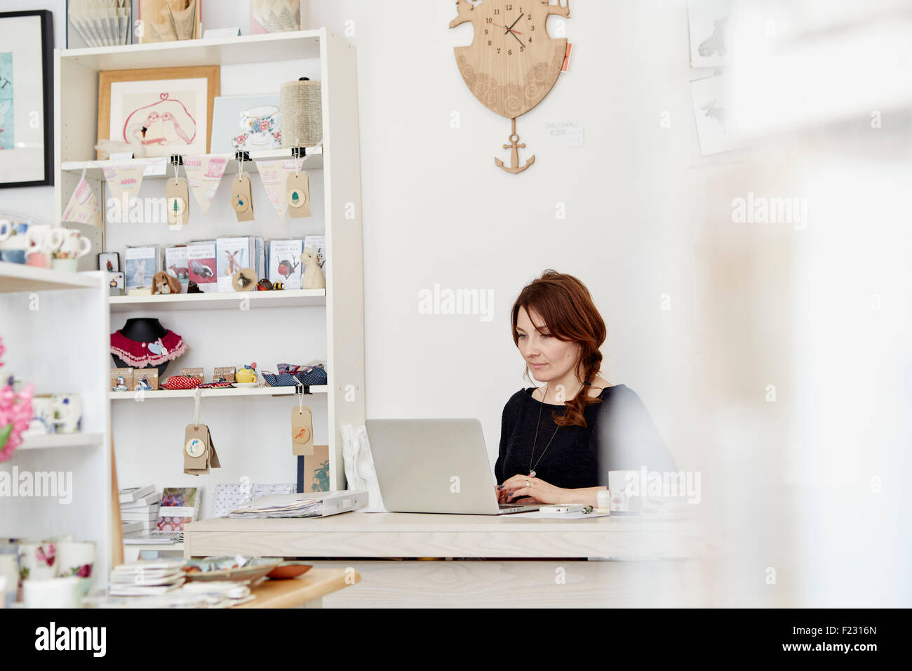 A woman sitting at a desk in a small gift shop, doing the paperwork, managing the business, using a laptop. - Stock Image