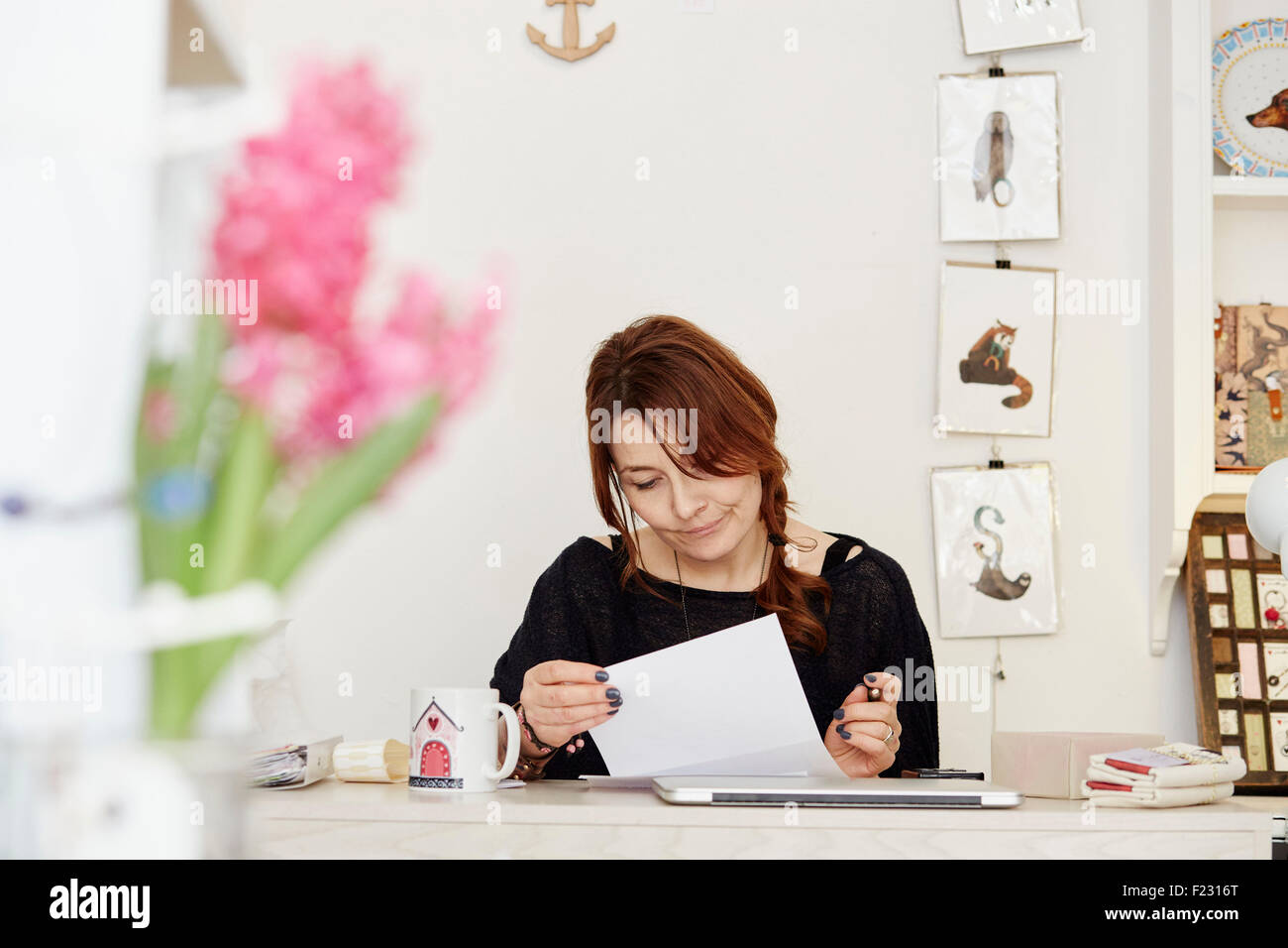 A woman sitting at a desk in a small gift shop, doing the paperwork, managing the business. A laptop on the desk. - Stock Image