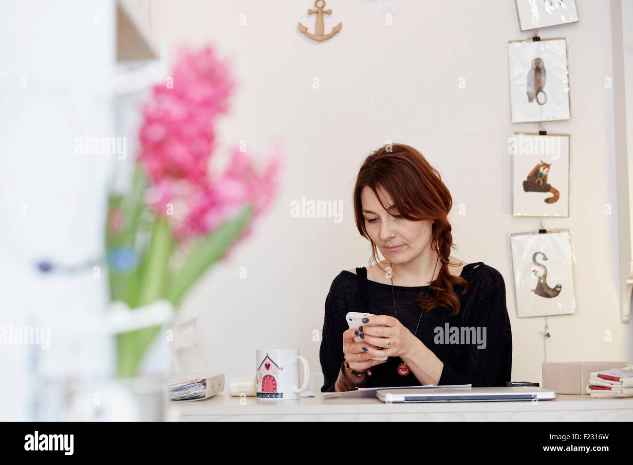 A woman sitting at a desk in a small gift shop, managing the business, making a call on a smart phone. - Stock Image