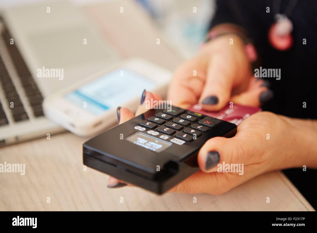 A woman's hands holding a credit card reader, processing payment or paying for goods. - Stock Image