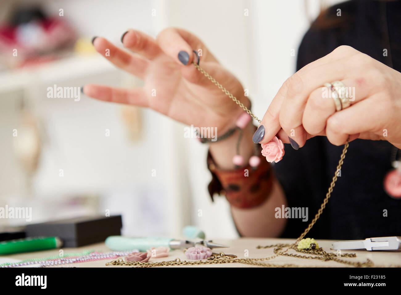 A woman seated at a workbench holding a gold chain with a small floral pendant, making jewellery. - Stock Image