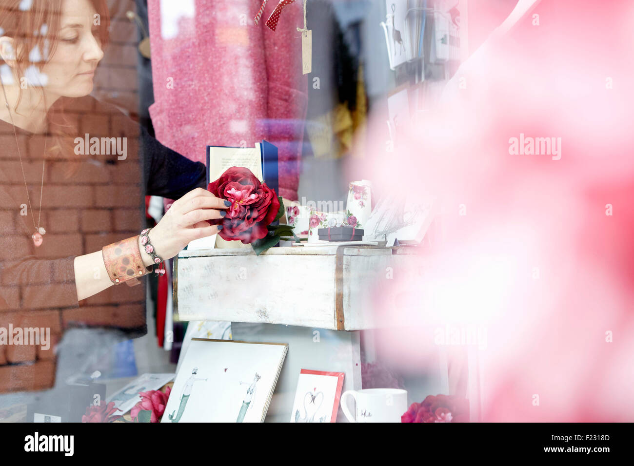 A mature woman rearranging the window display of a gift and craft store. - Stock Image
