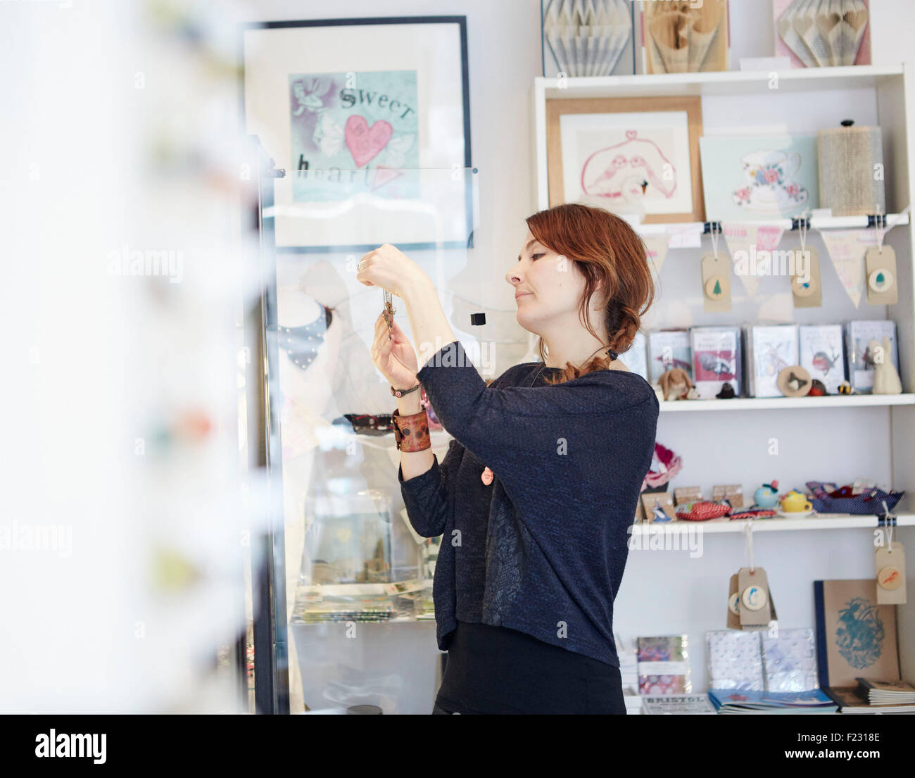 A mature woman in a gift and jewellery shop, looking closely at an object, a shopper or a business owner and jeweller. - Stock Image