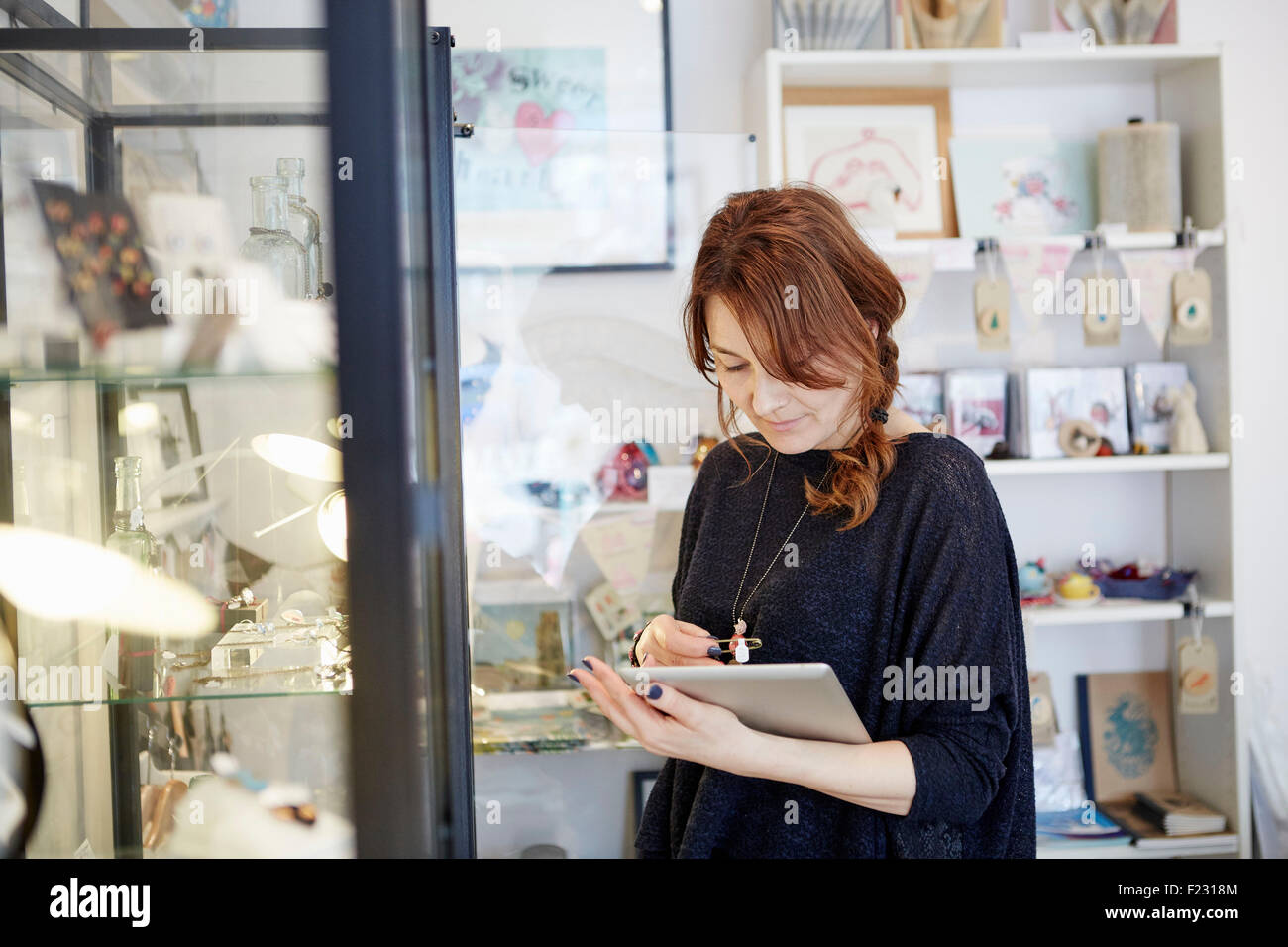 A mature woman using a digital tablet, using the touch screen, stock-taking in a small gift shop. - Stock Image