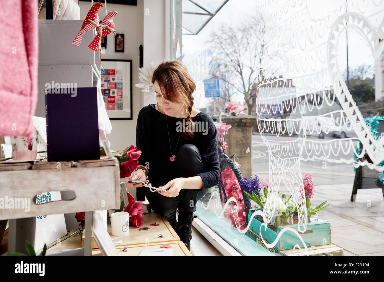 A mature woman in a gift shop by the window, holding a small star. - Stock Image