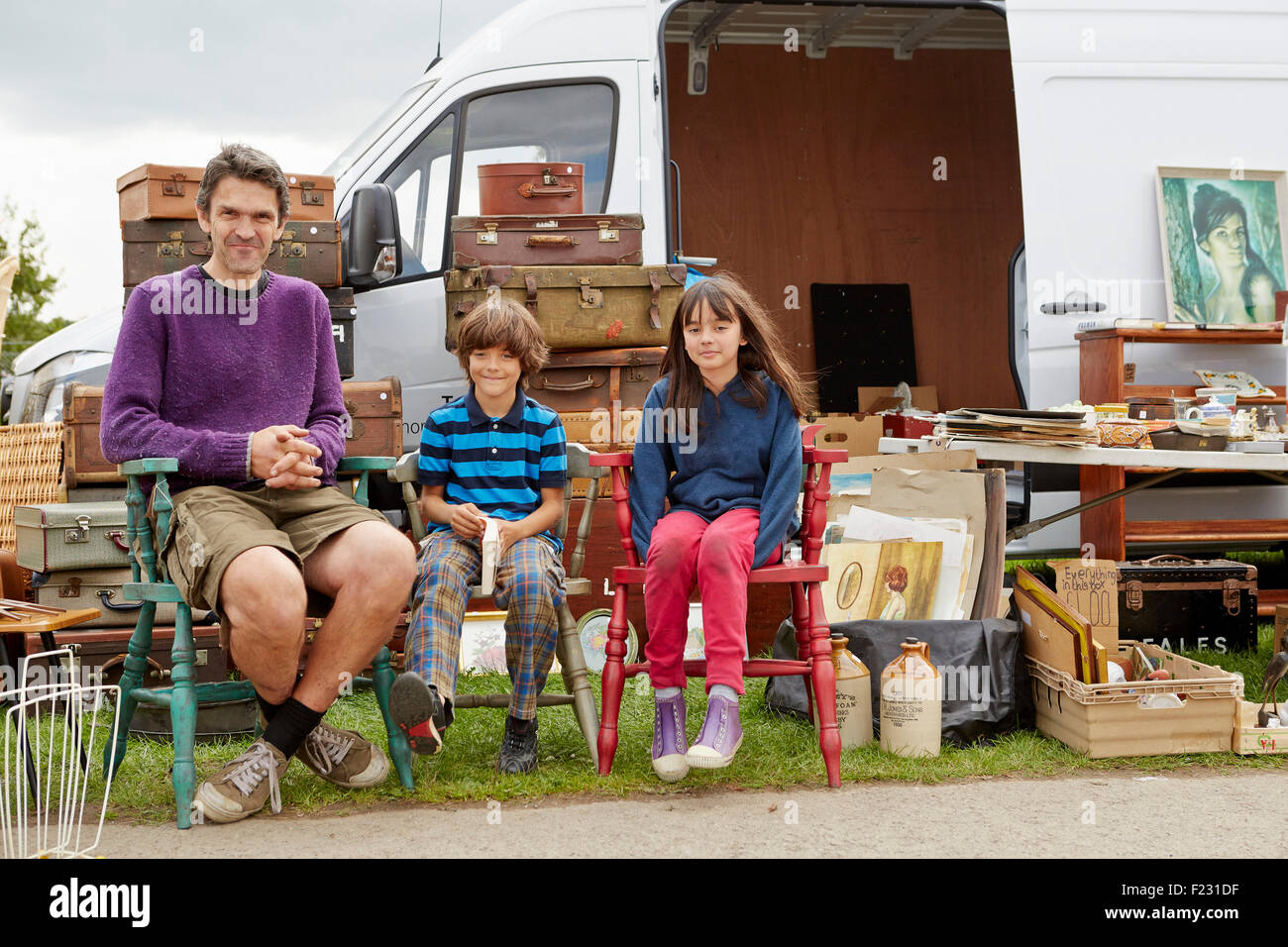 Man, boy and girl with trunks and baskets and furniture at flea market. - Stock Image