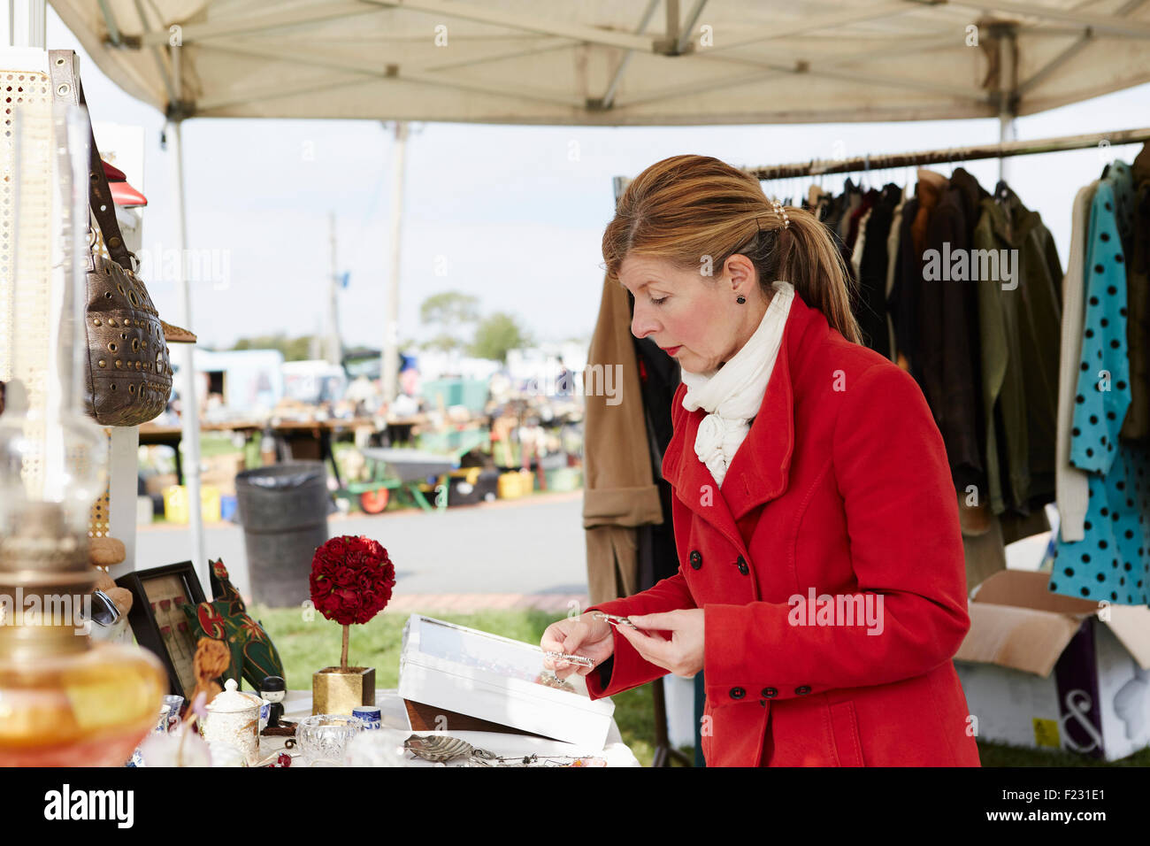 A mature woman bargain hunter browsing through vintage jewellery items at a clothing stall at a flea market. - Stock Image
